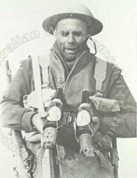 A soldier of the 6th Australian Division with a special kind of Italian anti-tank Molotov cocktail, consisting of a beer bottle and with petrol with a hand grenade tied to the bottom.