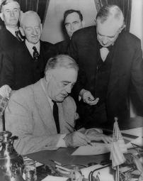 Roosevelt signing the declaration of war against Germany.
