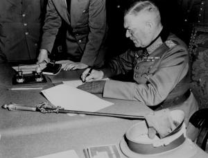 German Marshal Wilhelm Keitel at Russian Headquarters in Berlin signing the surrender document which declared that the hostilities would end next day.