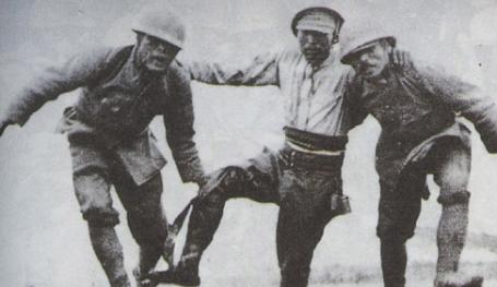 Two Japanese soldiers helping a wounded comrade off the battlefield near Suzhou Creek.