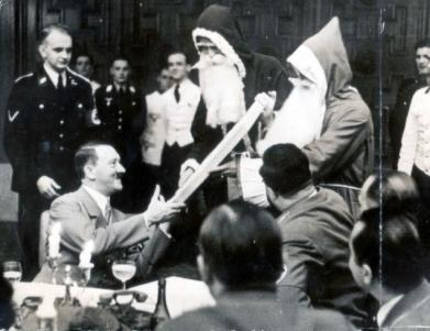 Fuhrer receives a present from two Santas while attending a Christmas party given by the Chief of the Chancellery.